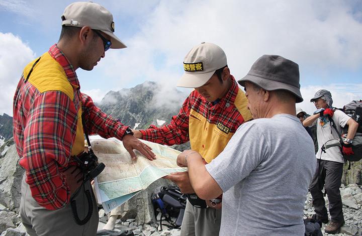 長野県警察山岳遭難救助隊隊長 宮﨑茂男さん 地図を見ながら、登山者にルートの説明をする救助隊隊員